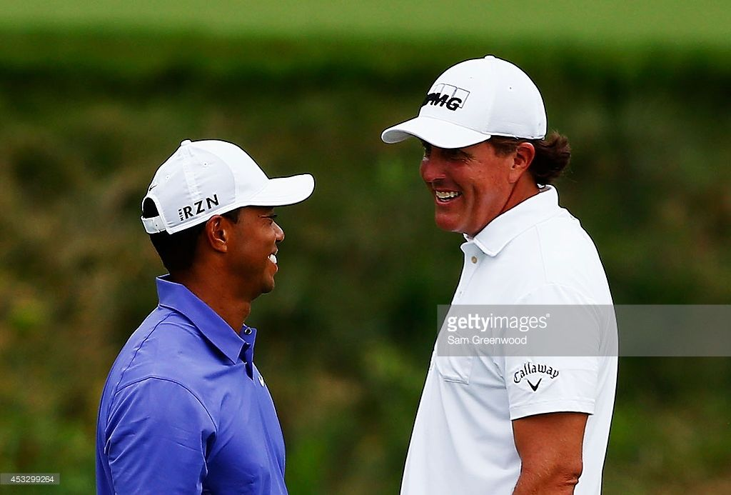 Tiger Woods of the United States reacts to Phil Mickelson as he walks off of the 18th green during the first round of the 144th Open Championship at The Old Course on July 16, 2015 in St Andrews, Scotland.