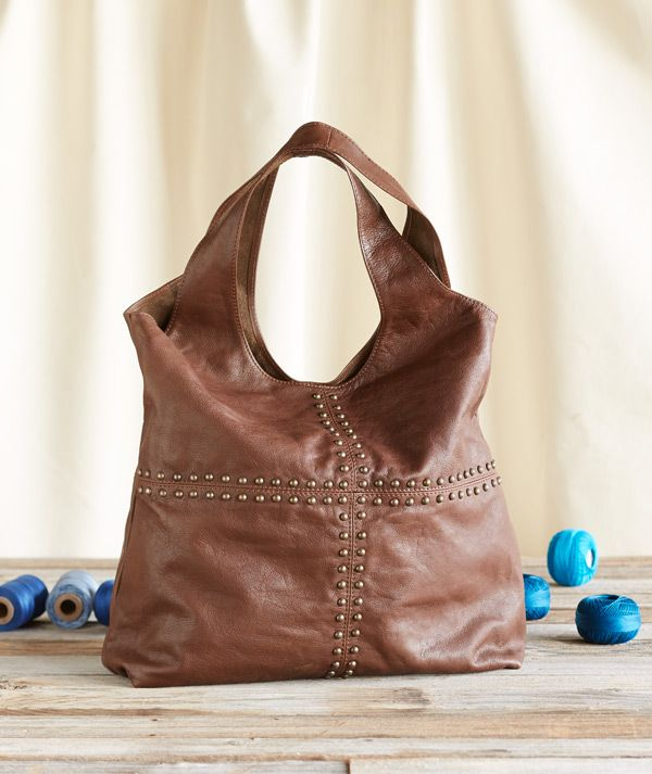 Bold and bright, brass studs dot our roomy, leather tote.