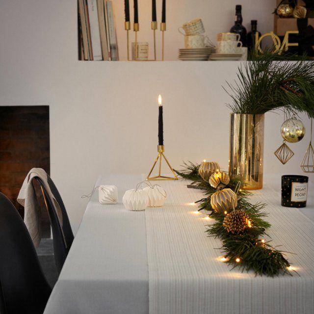 Une table de fête toute dorée chez H&M Home : on crée un joli chemin de table à l'aide de petites branches de sapin que l'on agrémente d'une fine guirlande lumineuse et de boules de Noël dorées. On ajoute un bougeoir doré et le tour est joué.