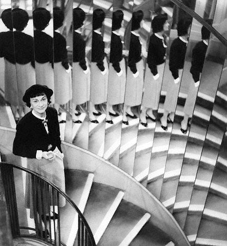 * Chanel, on the mirrored staircase of her couture house, photo by model and friend Suzy Parker, March 1, 1954, Paris