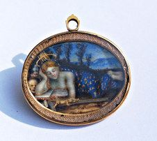 Unusual  pendant for lives lost at sea - a watercolor miniature on parchment, under crystal and set to a gold pendant, circa 1720. The miniature is of Stella Maris, protectress of mariners and seafarers. She is portrayed in her lapis blue robe covered in golden stars and wearing a golden starburst crown. The skull, urn and crucifix in the scene symbolize souls lost at sea.