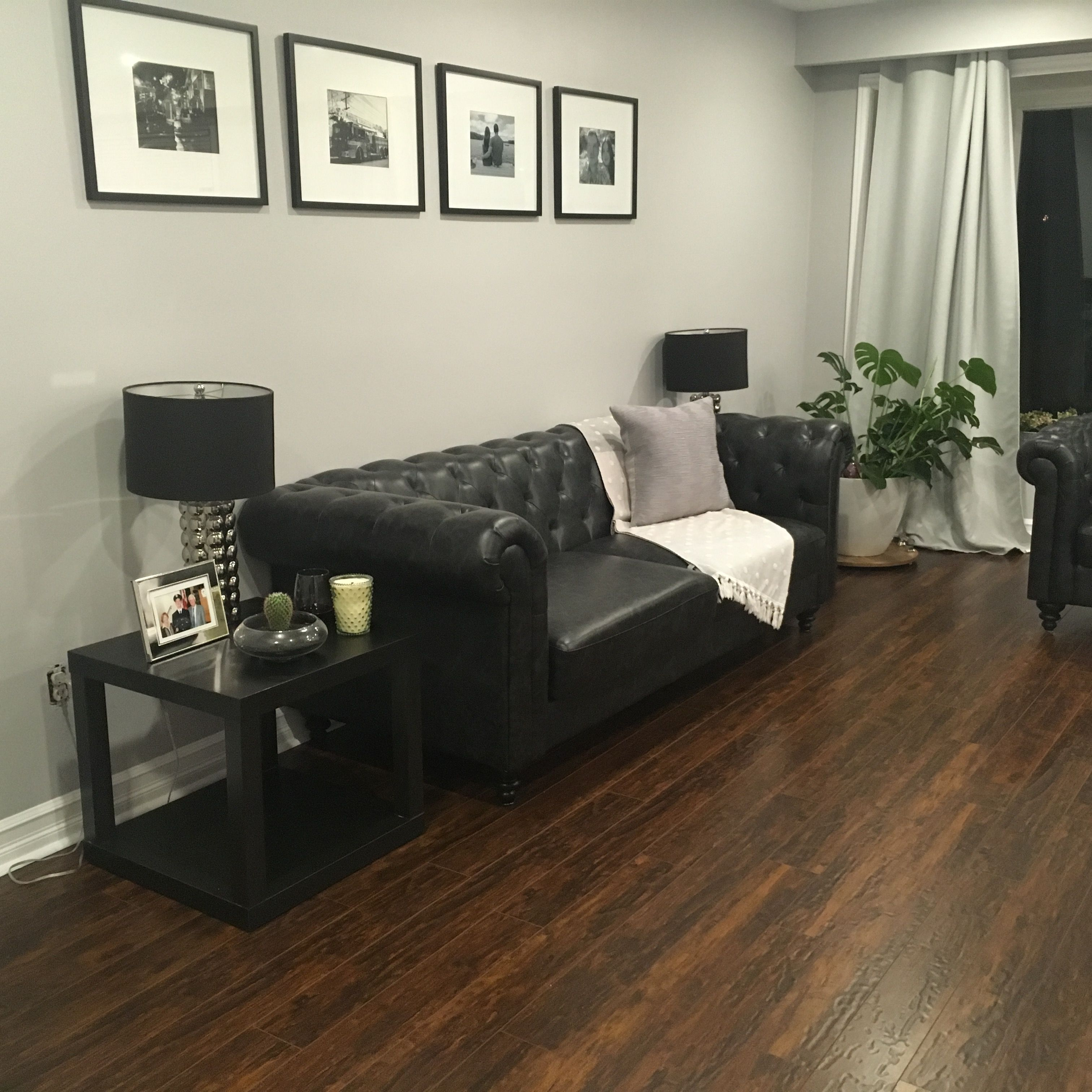 Updated 1960s Living Room Black Leather Sofa And Dark Hardwood