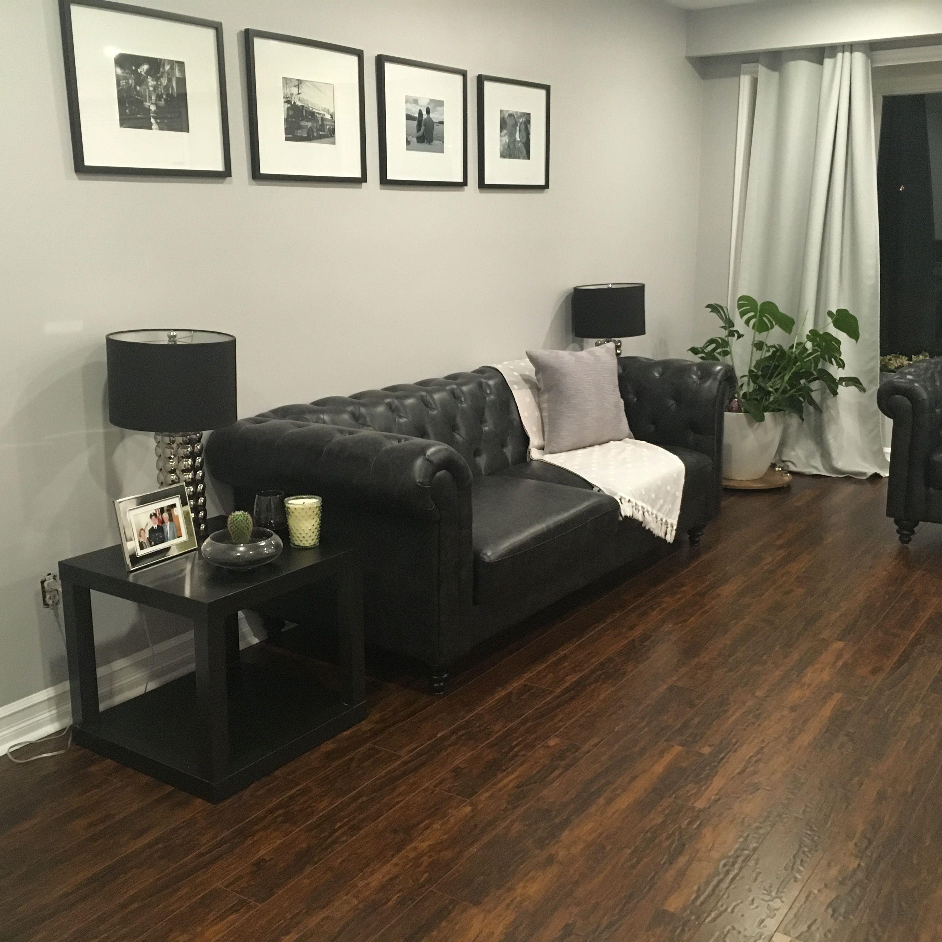 Black leather sofa and dark hardwood floor living room