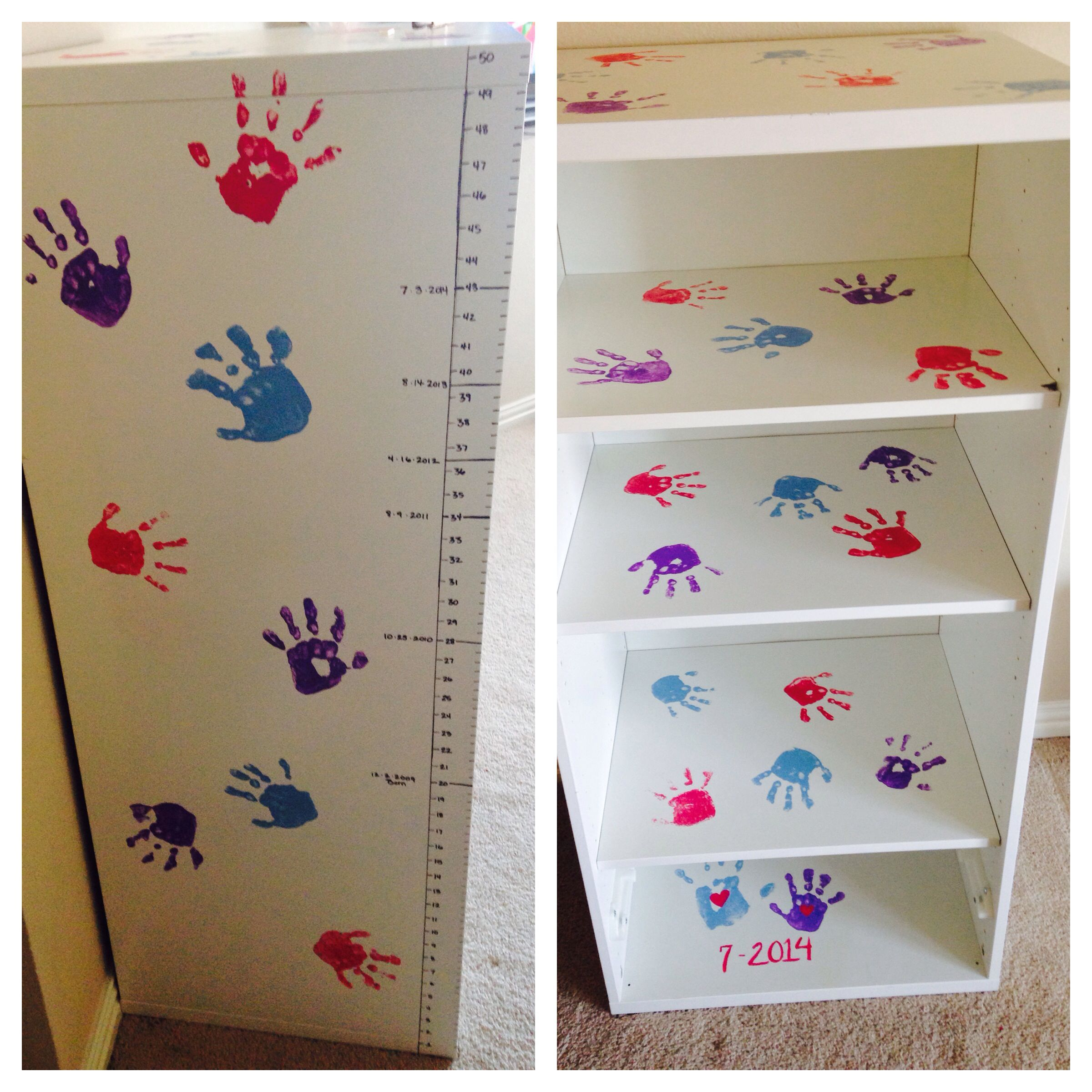 IKEA bookshelf makeover! Painted my daughters hands and did hand prints all over shelf. Put one of mine and her hand on inside bottom with little hearts in center of each. Drew in a measuring ruler and added height for each year. Will paint inside ruler varying colors for each measurement taken. Sprayed over everything with a glider coat to seal it in except area on ruler where she will continue to grow. :) Not bad for a playroom bookshelf!
