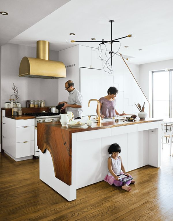 White kitchen, free cut wood draped over island, brass hood and faucet