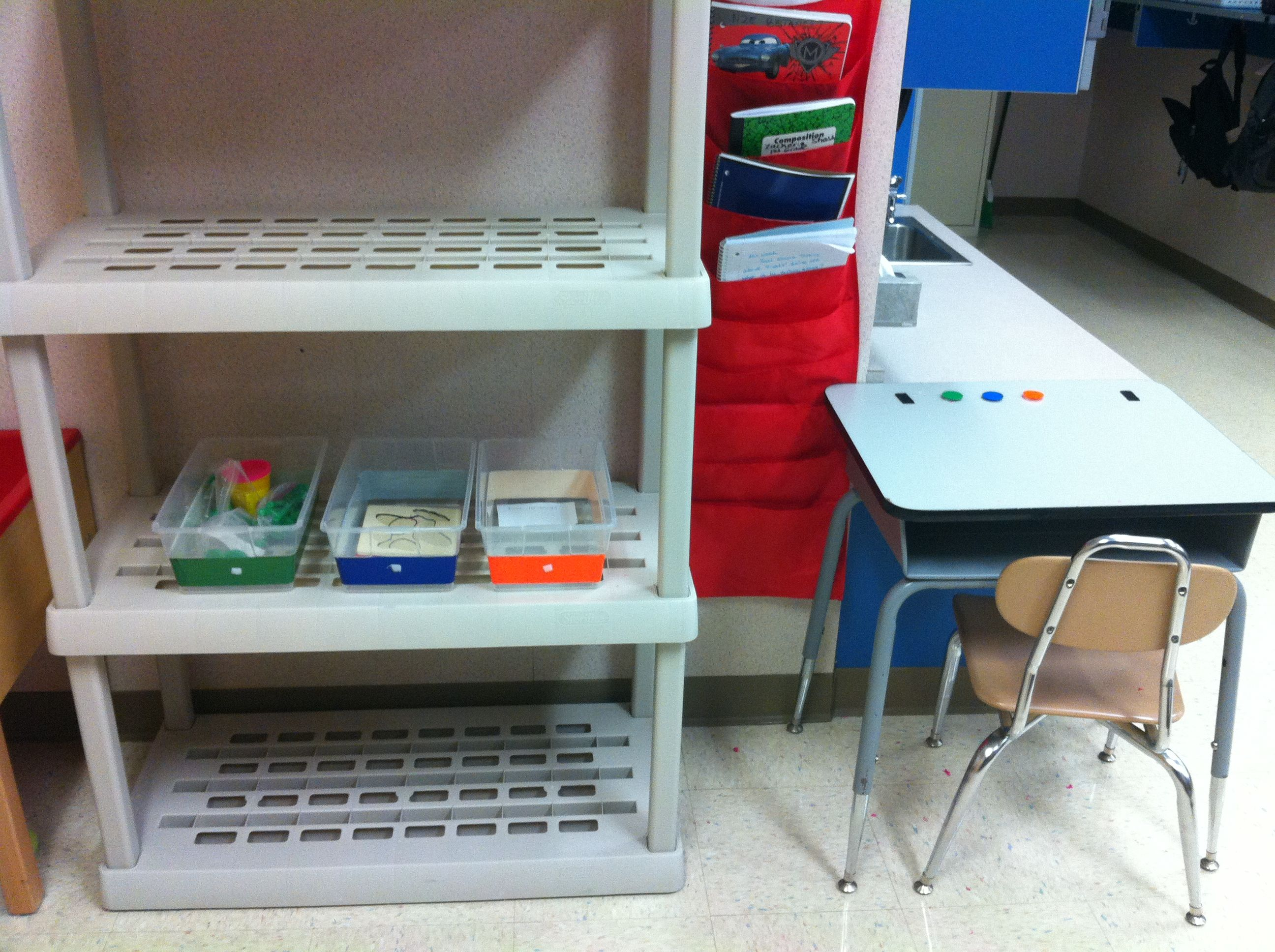 structured sensory area, work system on desk. Students work left to right, matching chips to colored bins. Sensory table to the left of shelves (TEACCH Philosophy)