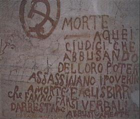 """Carceri di Vicopisano. Numerose scritte, specialmente nelle Carceri a Tetto, sono dipinte con un inchiostro rossastro, che i detenuti ottenevano polverizzando il pavimento in cotto delle celle e mescolandolo con l'acqua. """"Morte aquei giudici che abbusando del loro potere assassinano i poverini a morte e agli sbirri che fanno farsi verbali e darrestano abbisivamente""""  FONTE: http://www.ecn.org/filiarmonici/vicopisano.html"""