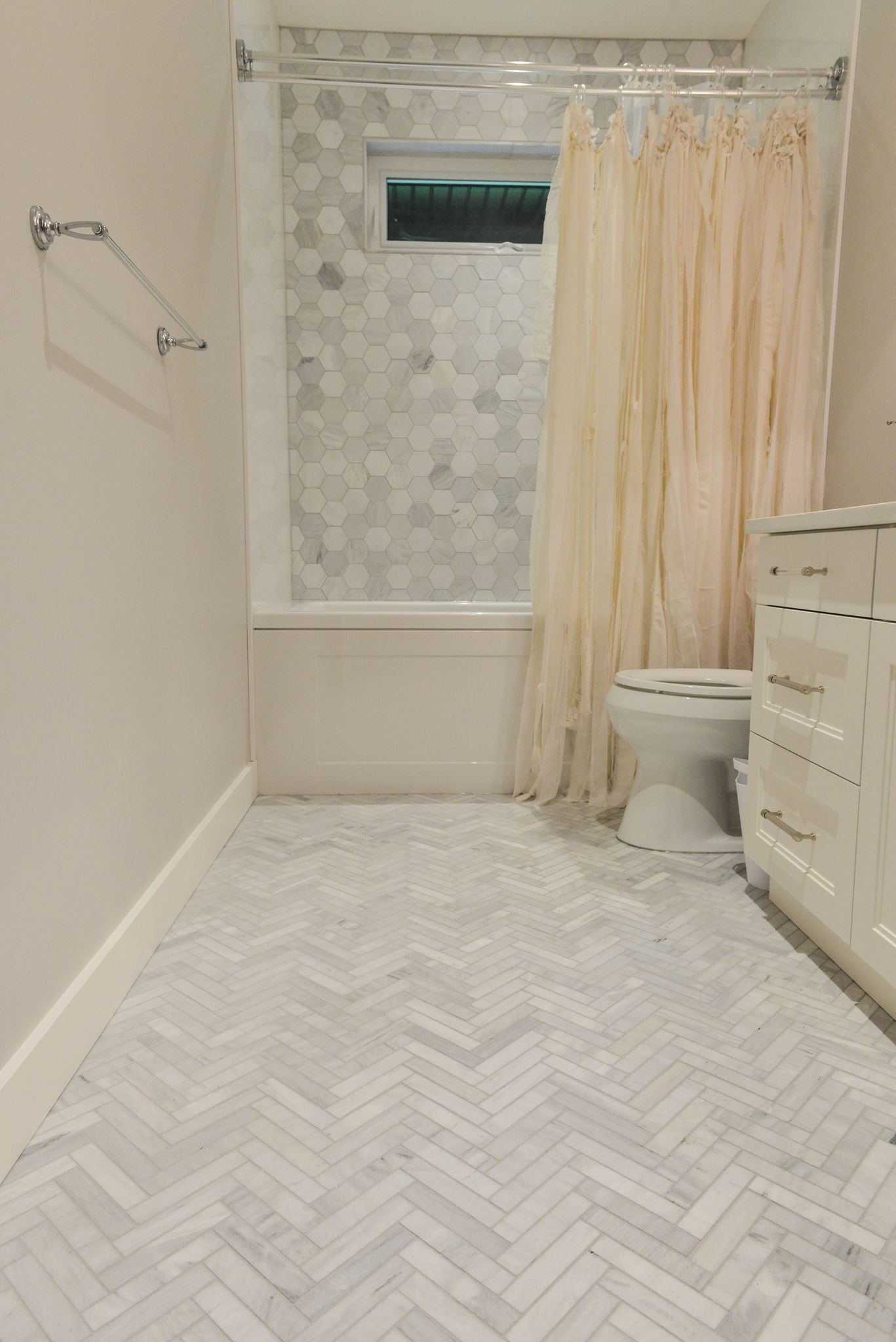 Grey marble tile in herringbone pattern on floor grey marble hexagon tile on shower wall Marble hex tile bathroom floor