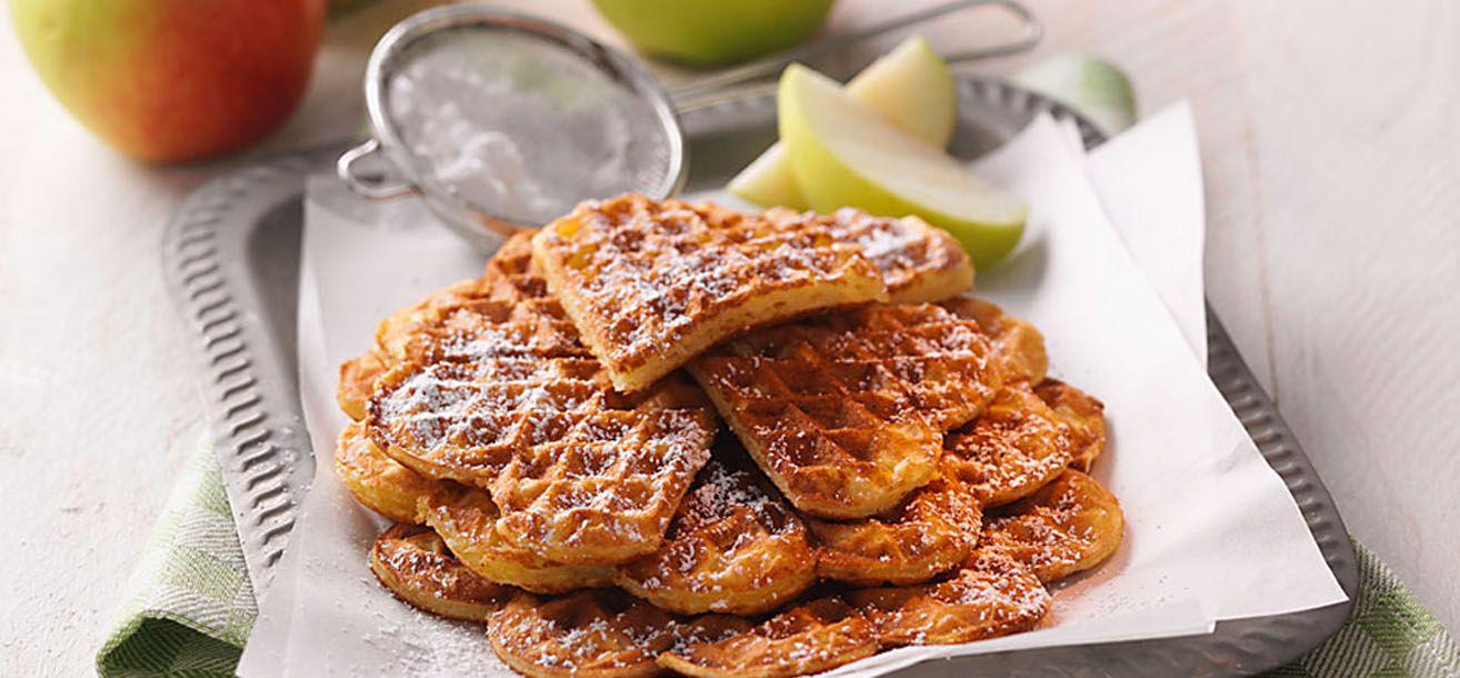 Die Äpfel waschen, schälen und raspeln. Die Butter mit SteviaZucker schaumig schlagen. Erst Eigelbe, Mehl und Buttermilch, dann Äpfel, Zimt und Mandeln unterrühren. Eiweiß steif schlagen und vorsichtig unter den Teig heben.    Das Waffeleisen vorheizen und mit Öl bestreichen. Jeweils 2-3 EL Teig hinein geben, Deckel schließen und 2-3 Minuten goldbraun backen. Nach Belieben mit Puderzucker dekorieren und heiß servieren.