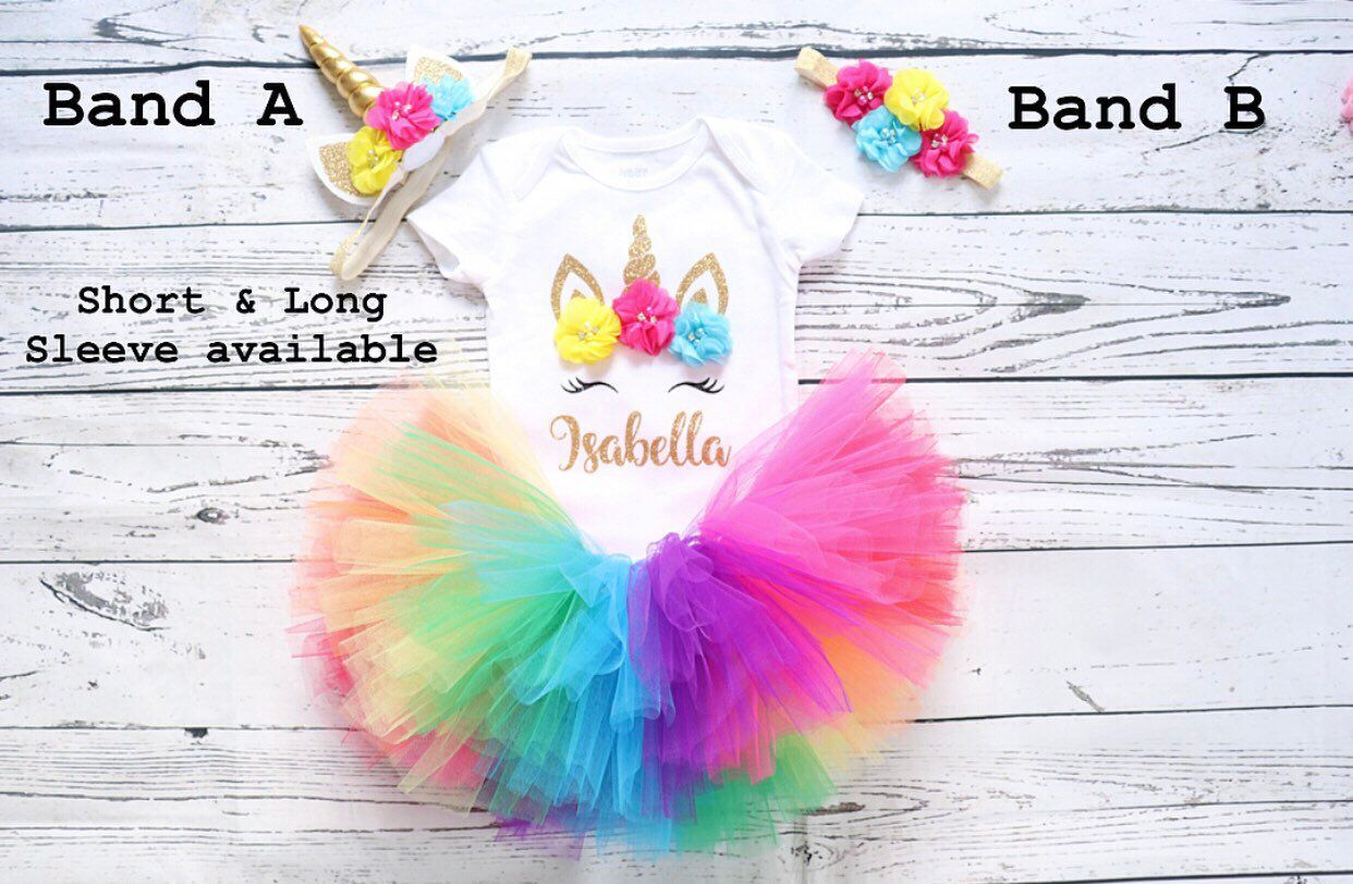 Rainbow Unicorn Birthday outfit rainbow unicorn bodysuit first birthday unicorn outfit baby girl birthday outfit 1st birthday unicorn outfit - Unicorn birthday outfit, Rainbow unicorn birthday, Baby girl birthday outfit, Birthday outfit, Birthday girl outfit, Baby girl birthday - A Personalized unicorn outfit made to order for your little one so she can sparkle on her big day   This outfit consists of four pieces; Top, Tutu, unicorn headband and a flower headband  We make each outfit to order so please leave us a note with your little one's name and your preferred sleeve length, we offer both short and long sleeve   The top will have a unicorn print on it using nonshed glitter material and three beautiful fabric flowers with pearls and rhinestones inside them  We use bodysuits for sizes up to 24 months and a regular shirt for sizes 2T5T   Tutu consists of seven different colors Red, Hot pink, Purple, Blue, Green, Yellow and Orange  If you would like to add or change the colors please leave us a not when you make your order, we are more than happy to do so  The Tutu comes in different lengths depending on the shirt size you choose  Preemie sizes up to 18m 6 inch long tutu  24m3T 8 inch long tutu  4T5T 10 inch long tutu   We offer two different headband with this outfit  Unicorn headband that comes with three matching delicate fabric flowers all attached on a gold band    A floral headband which comes  with three different fabric flowers to complement each of the flowers that are on the shirt perfectly, all arranged on a beautiful stretchy gold band   Once you make you order we send it out within 13 business days  If you are tight on time and need it sooner, please leave us a note when you make your order and we will process it accordingly   All orders are shipped through USPS unless you would like it differently, Shipping is usually 25 business days  You can upgrade to priority shipping if you need it sooner  Please feel free to message me with any questions, I am al