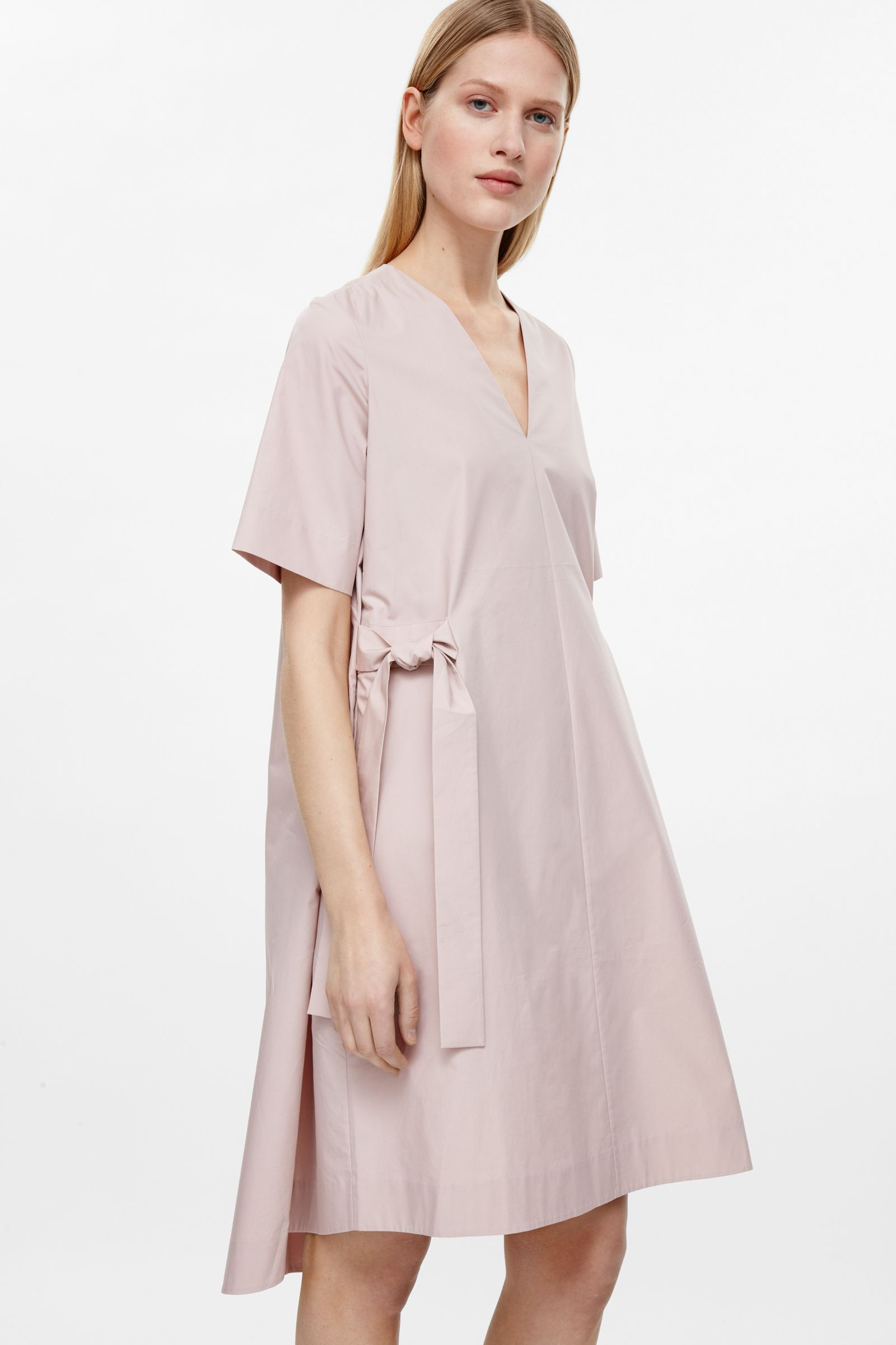 Coming in at the waist this vneck dress has tie belts on either