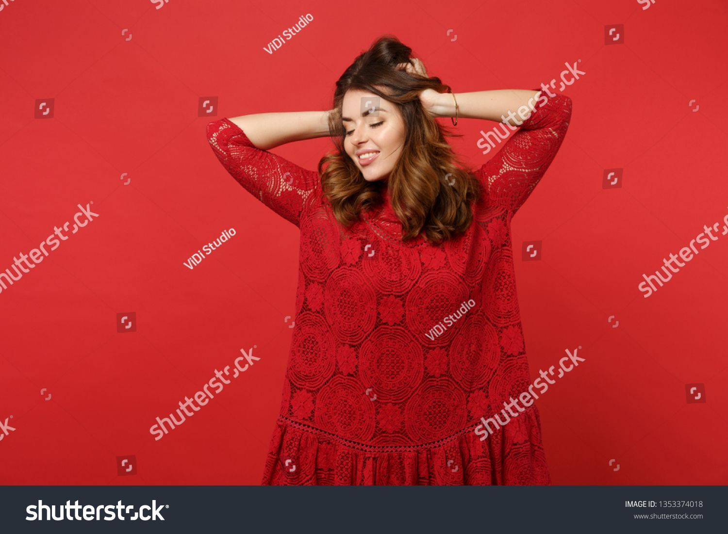 Portrait of charming young woman in lace dress keeping eyes closed putting hands on head isolated on bright red background in studio People sincere emotions lifestyle con...
