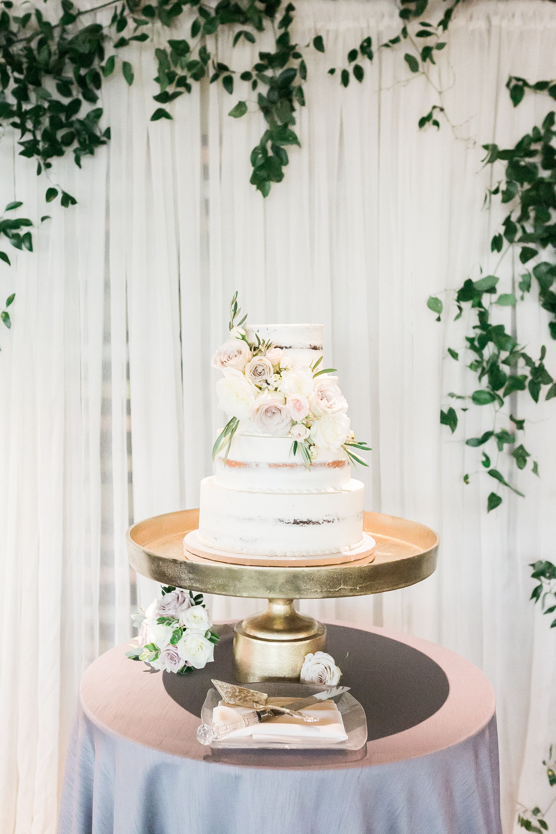 Cake with fresh flowers displayed in front of draping and greenery