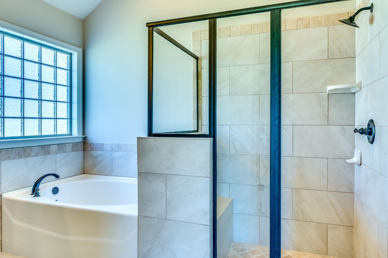 Stunning master bathroom with tan walls along with a large bath tub ...