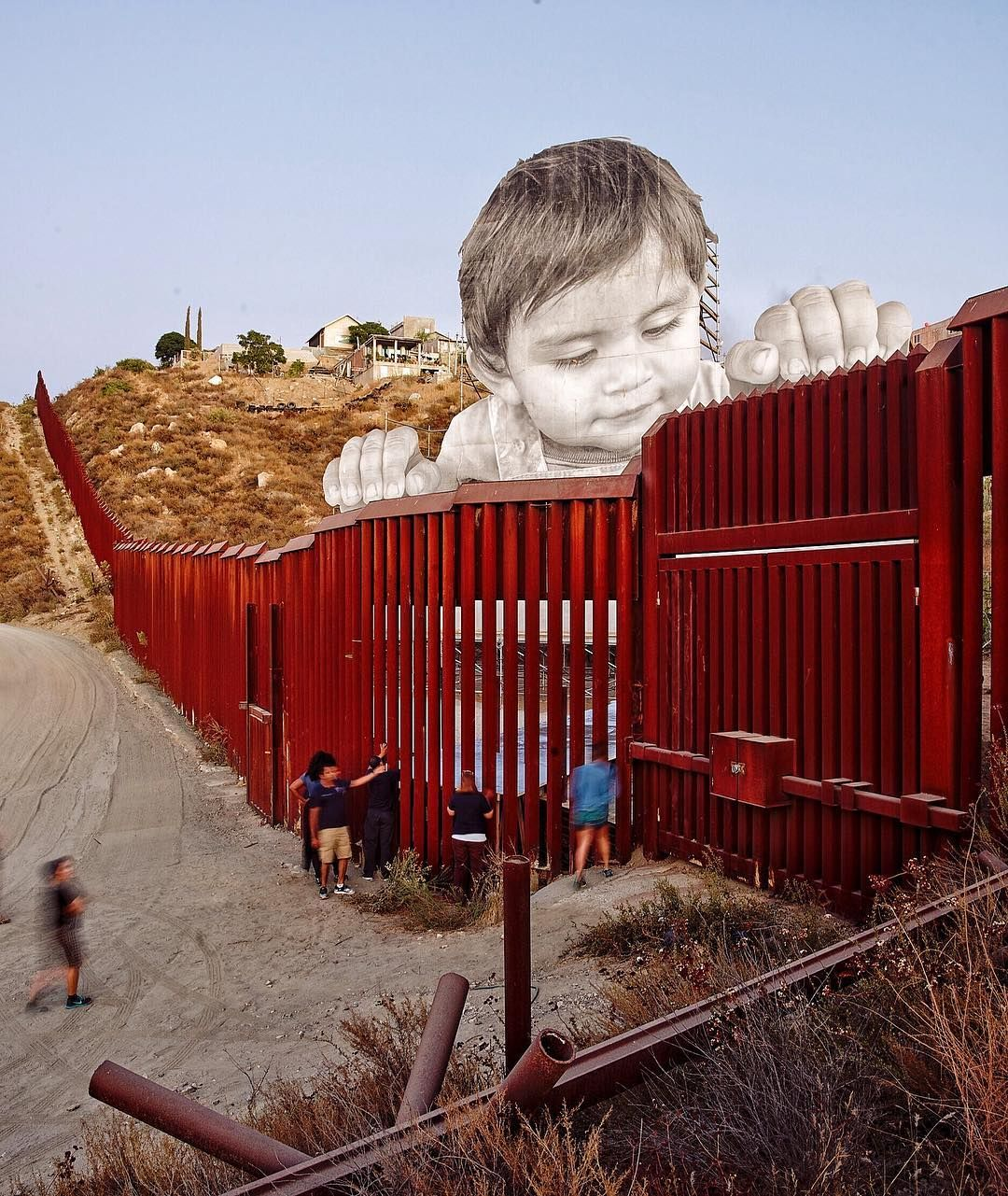 JR installed massive face of a child on mexican side of US