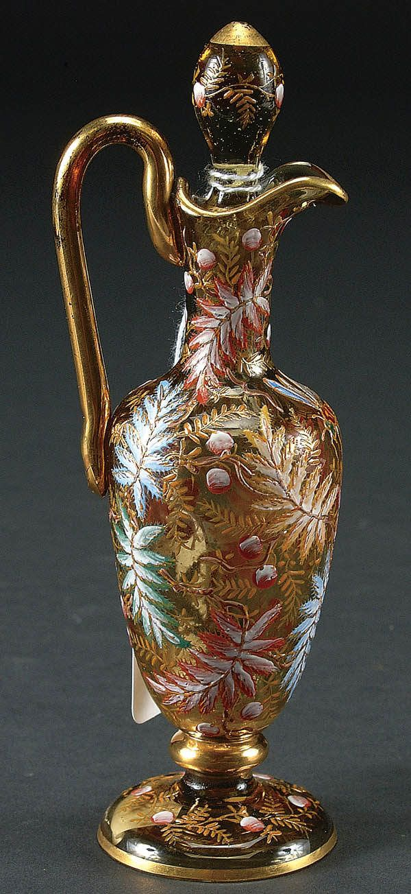 A GOOD MOSER ENAMELED GLASS CRUET circa 1890 with fern, berry and insect decoration on topaz colored glass. Retains partial Moser Carlsbad label. Height 6.5 inches.