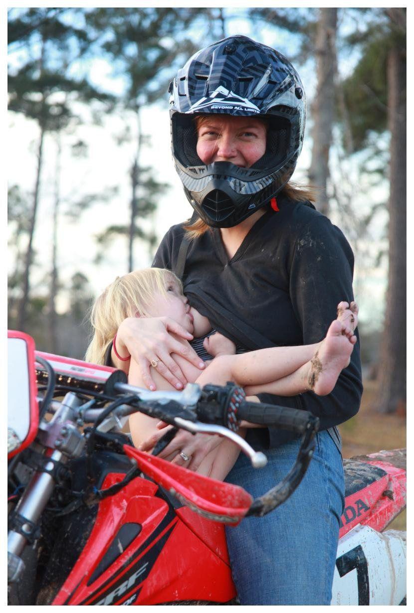 Breastfeeding on a dirt bike. She's nakey b/c she had been