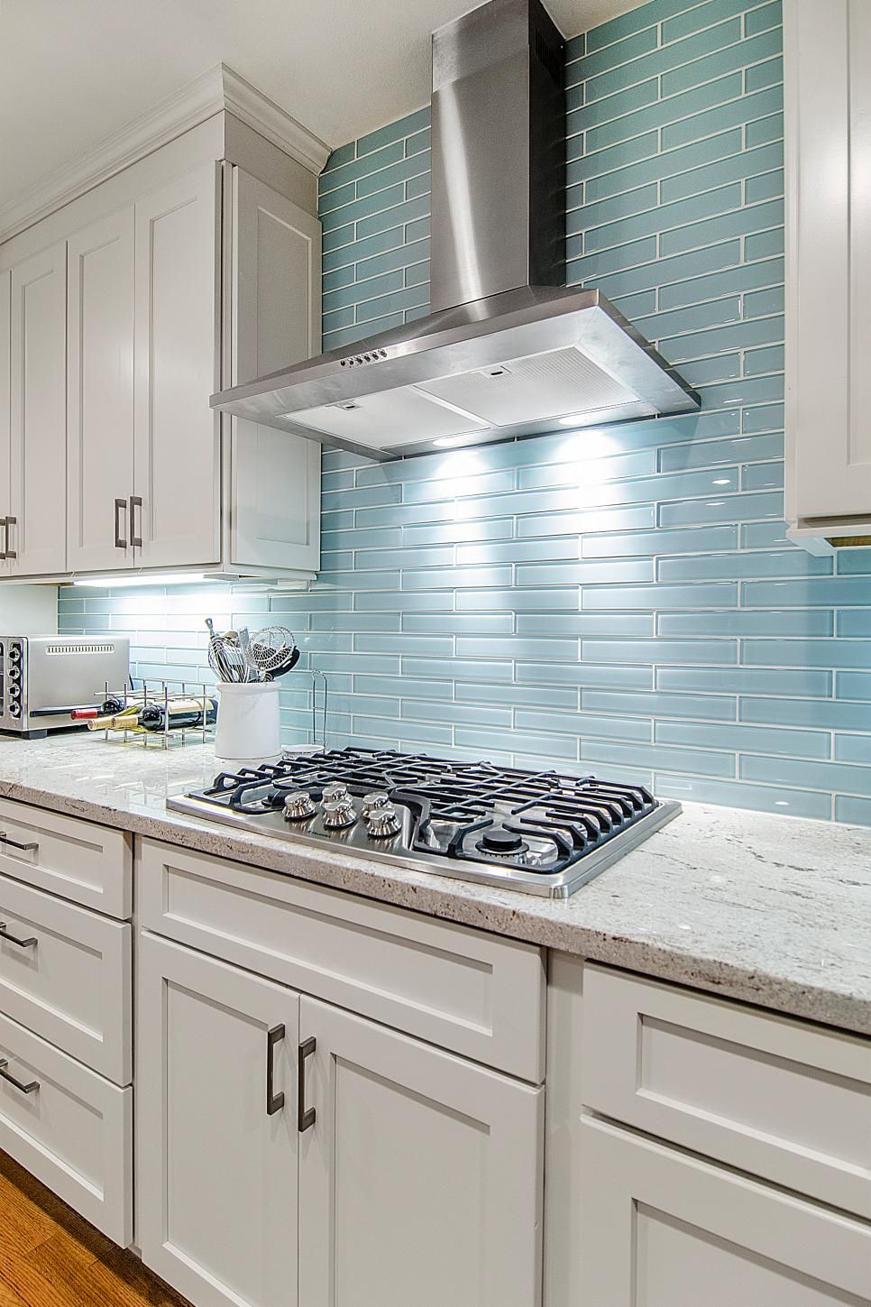 The reflective quality of this kitchen\'s blue glass tile backsplash ...