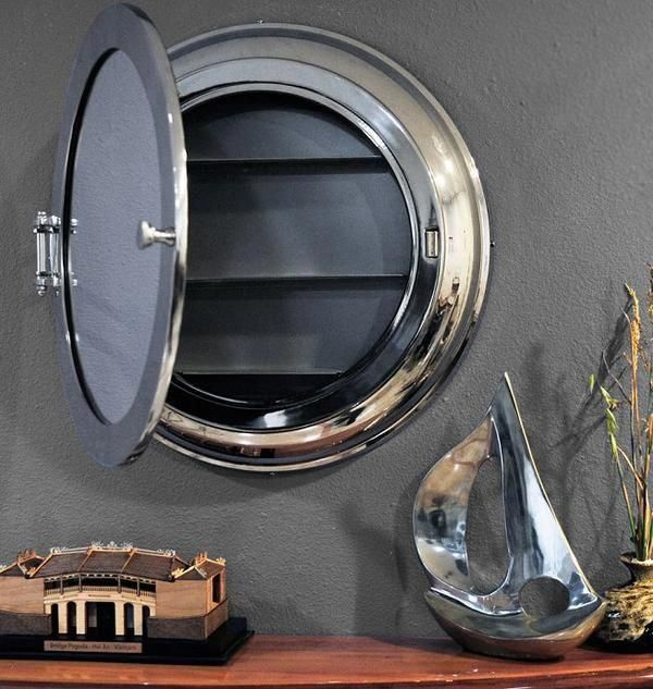 """A vintage style porthole is converted into a nautical decor accent with our Stateroom Porthole Cabinet Storage Mirror. Cast from aluminum, it features a polished nickel finish. The mirror front is hingedand features a knob pull for easy opening. Inside isa small storage compartment with three narrow fixed shelves. It's perfect for your nautical-themed powder room or onboard stateroom. Entire piecemeasures: 21""""H x 21""""W x 3.5""""DMirror face measures: 14″ diameter ***THIS POPULAR ITEM IS ON BACKORDER. SHIPS IN NOVEMBER.***"""