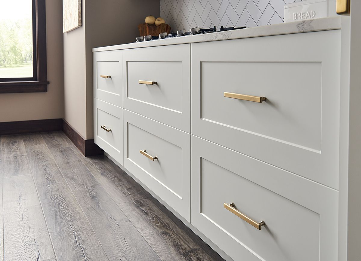 Creamy white shaker cabinets with gold hardware Shaker