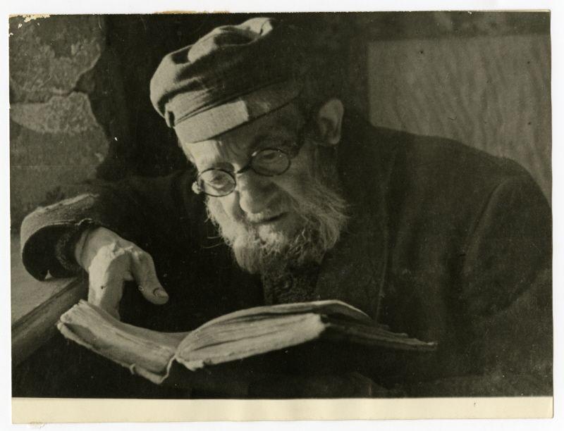 Shmuel Dawid Grosman reads a book [probably in the Lodz ghetto].