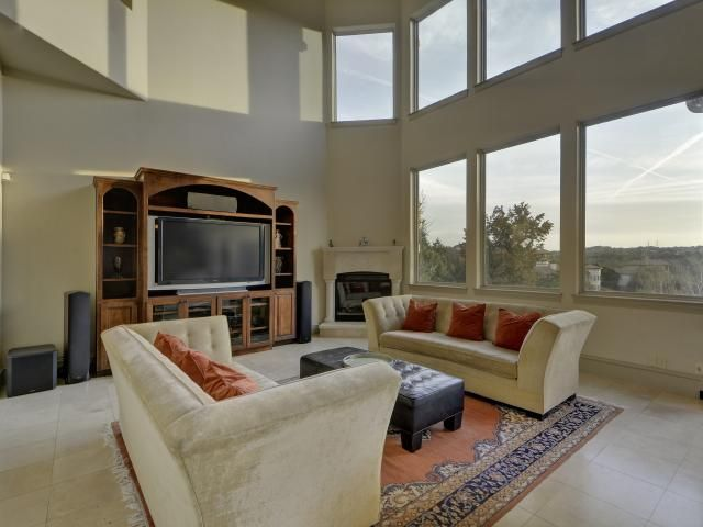 Two story, open living room with floor to ceiling windows that provide lots of natural light 103 Arroyo Claro, Lakeway Texas 78734