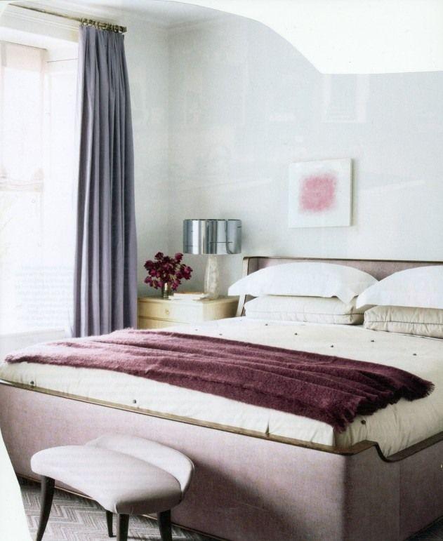 une couverture en lilas et des rideaux bleus dans la chambre à coucher blanche