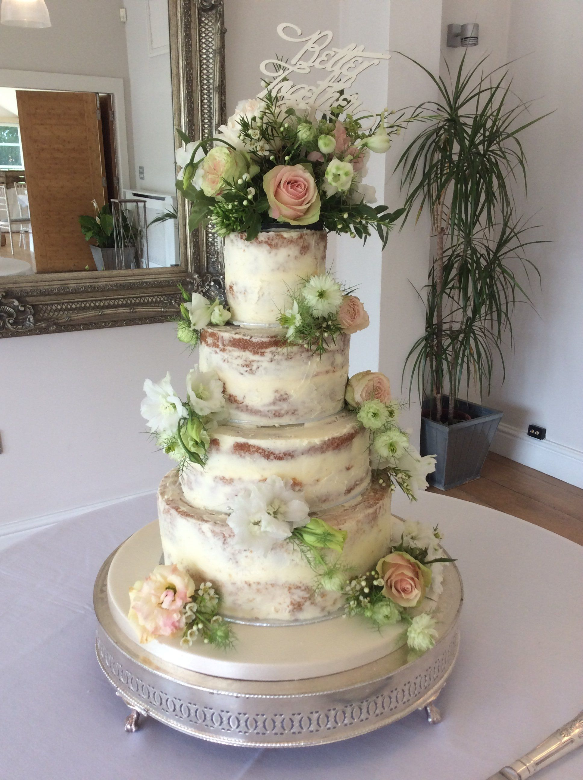 4 tier Semi Naked wedding cake decorated with fresh