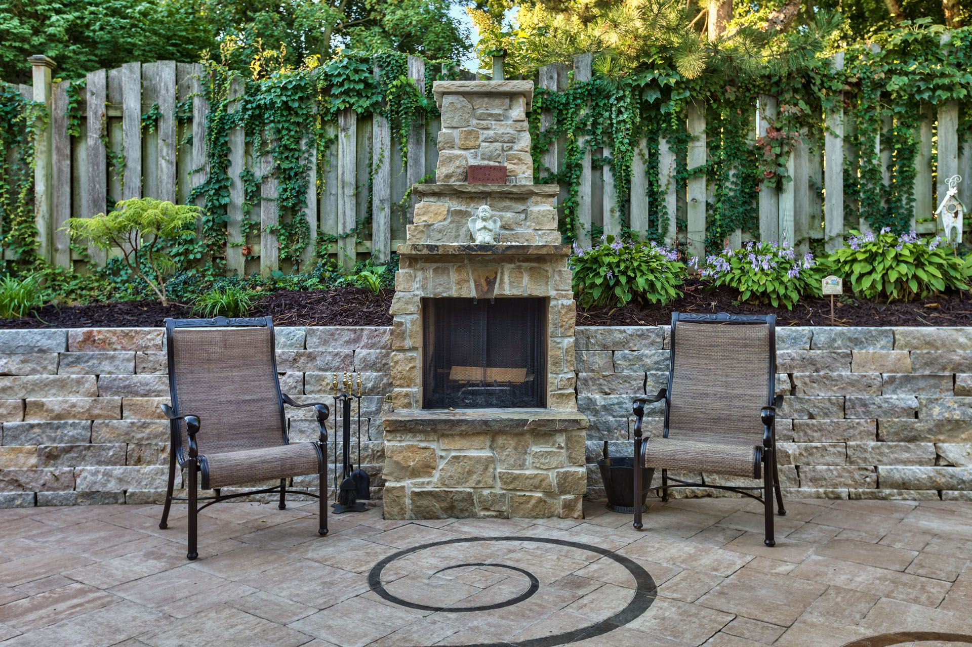 An elegant stone fireplace was built into a retaining wall to make
