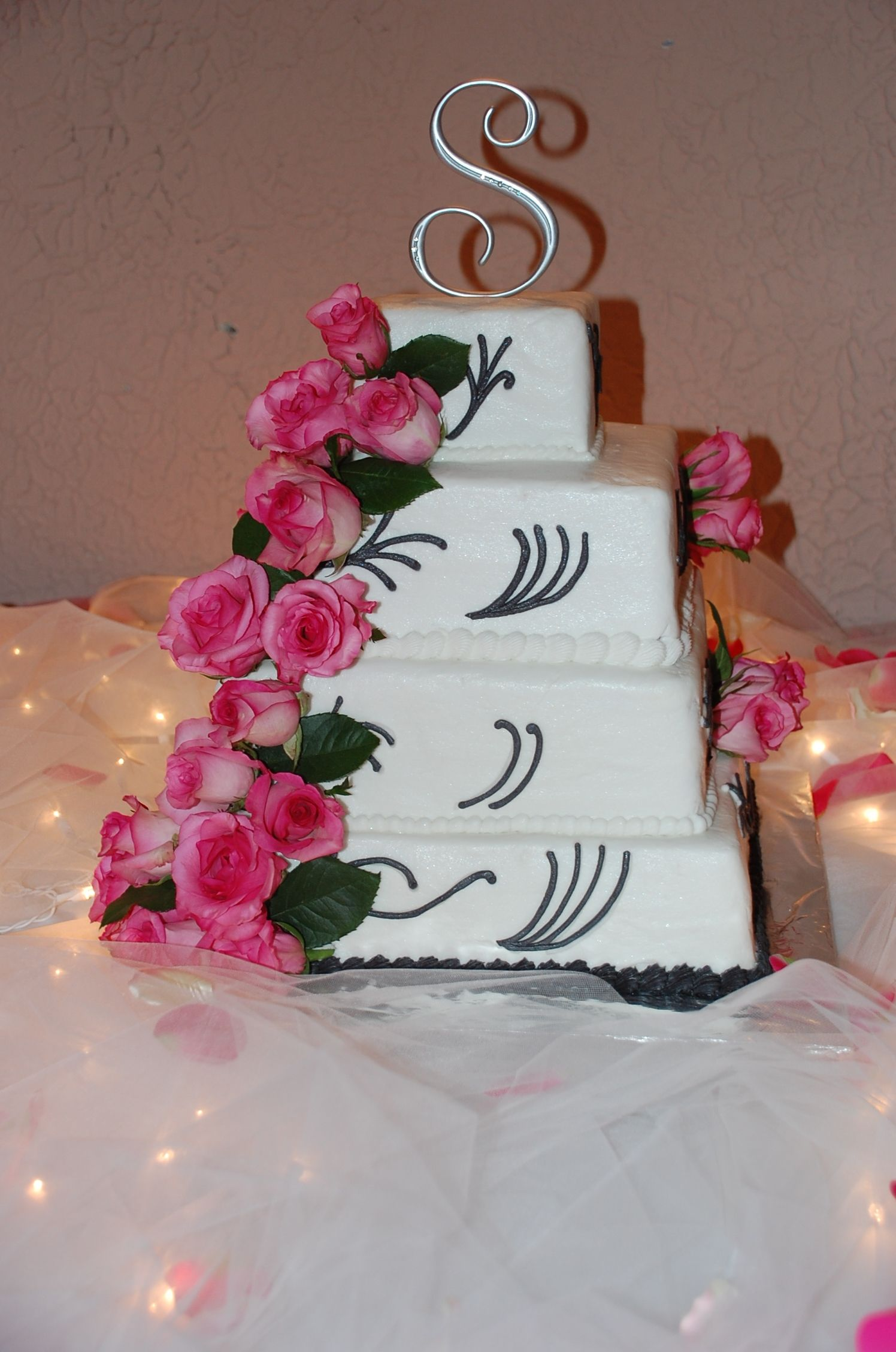 Wedding cake with real roses love the lights under the table cloth