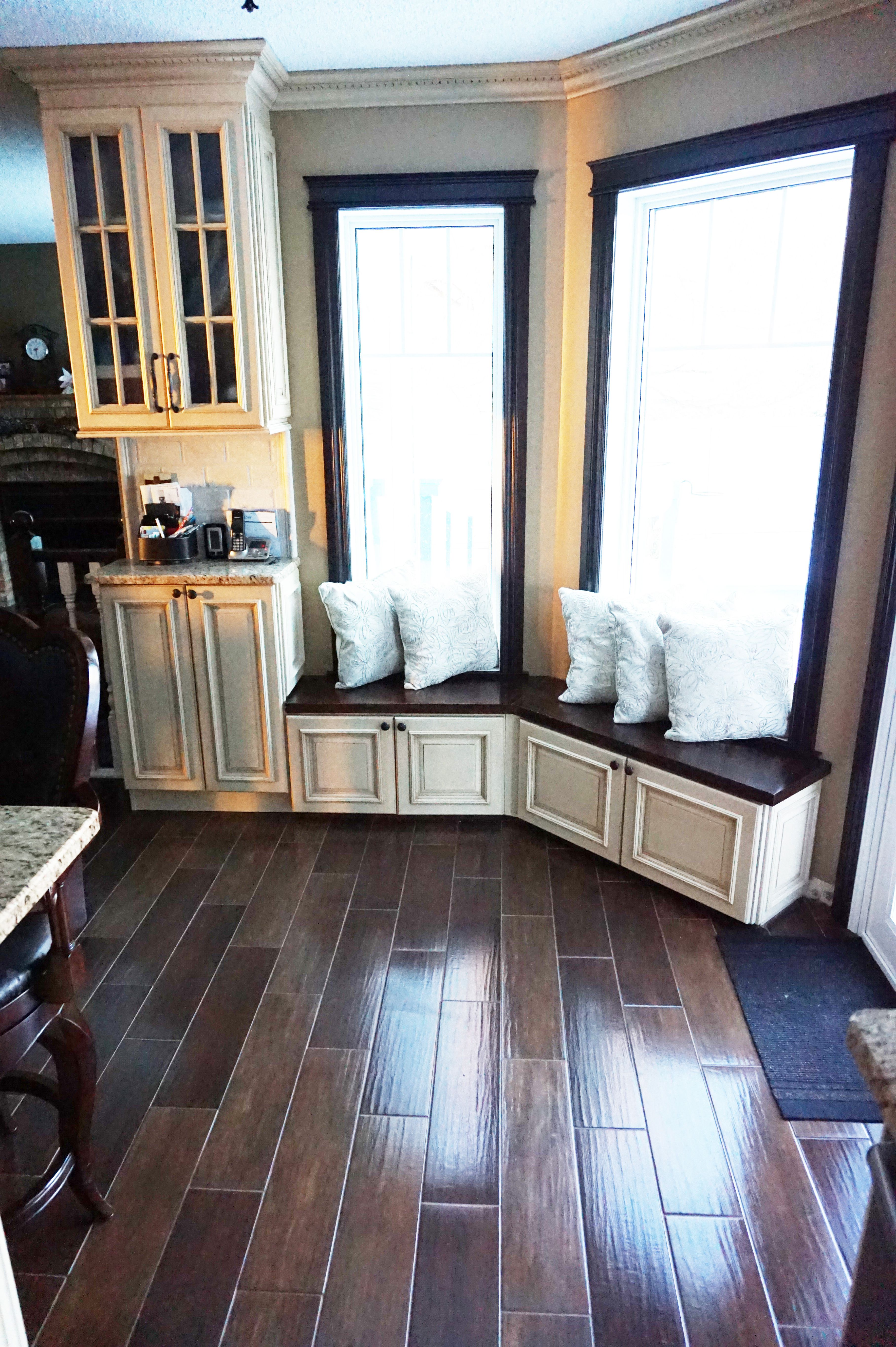 Window under kitchen cabinets  seating created by using wall cabinets would have never thought of