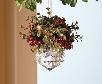Old European tradition considers mistletoe a magical plant that grants strength, peace, health, love, and fertility to those who kiss beneath it. Gold-glittered leave and red berries hang over a sparkling centerpiece.