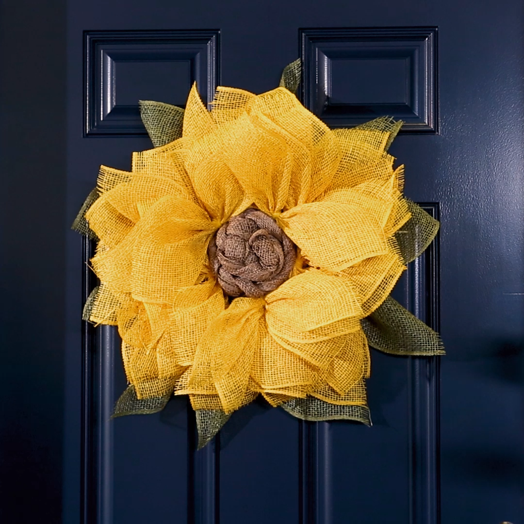 This sunflower burlap wreath easily transitions from spring to fall and comes together in under an hour! Using basic crafting materials like burlap ribbon, pipe cleaners, and a wire wreath form this simple DIY burlap wreath is a gorgeous floral-inspired door hanging. #burlapwreath #diywreath #sunflowerwreath #springwreathideas #howtomakeaburlapwreath #bhg