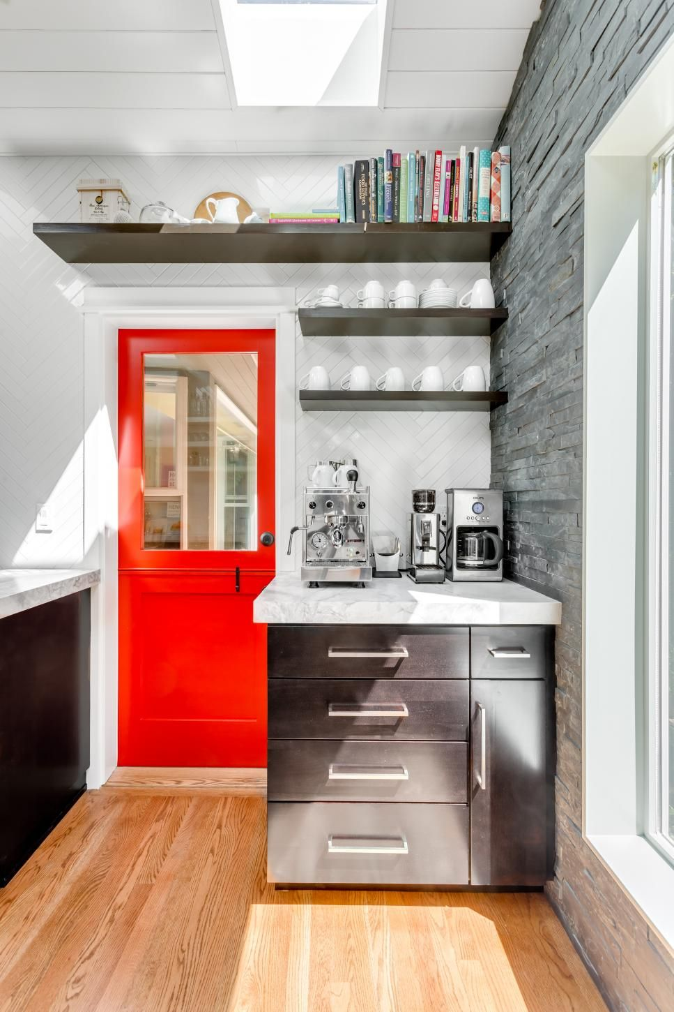 A bright red dutch door adds a fun splash of color to this neutral kitchen the contemporary space is full of natural light thanks to skylights