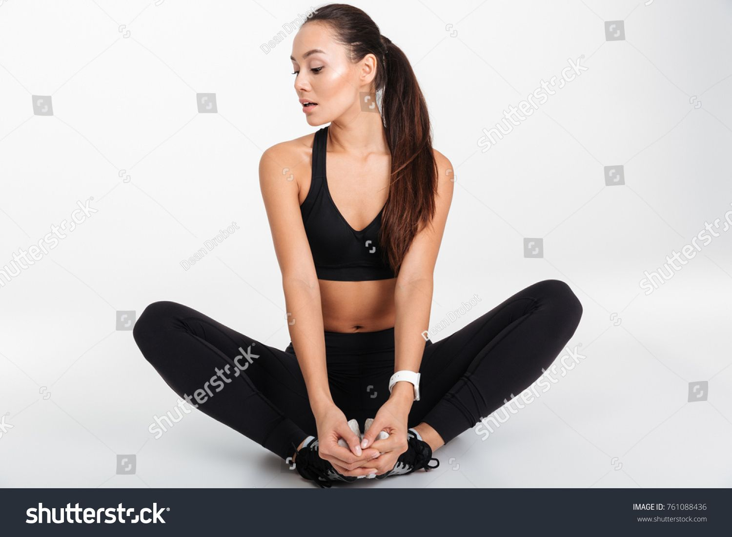 Portrait of a pretty asian fitness woman stretching her legs while sitting isolated over white backg...