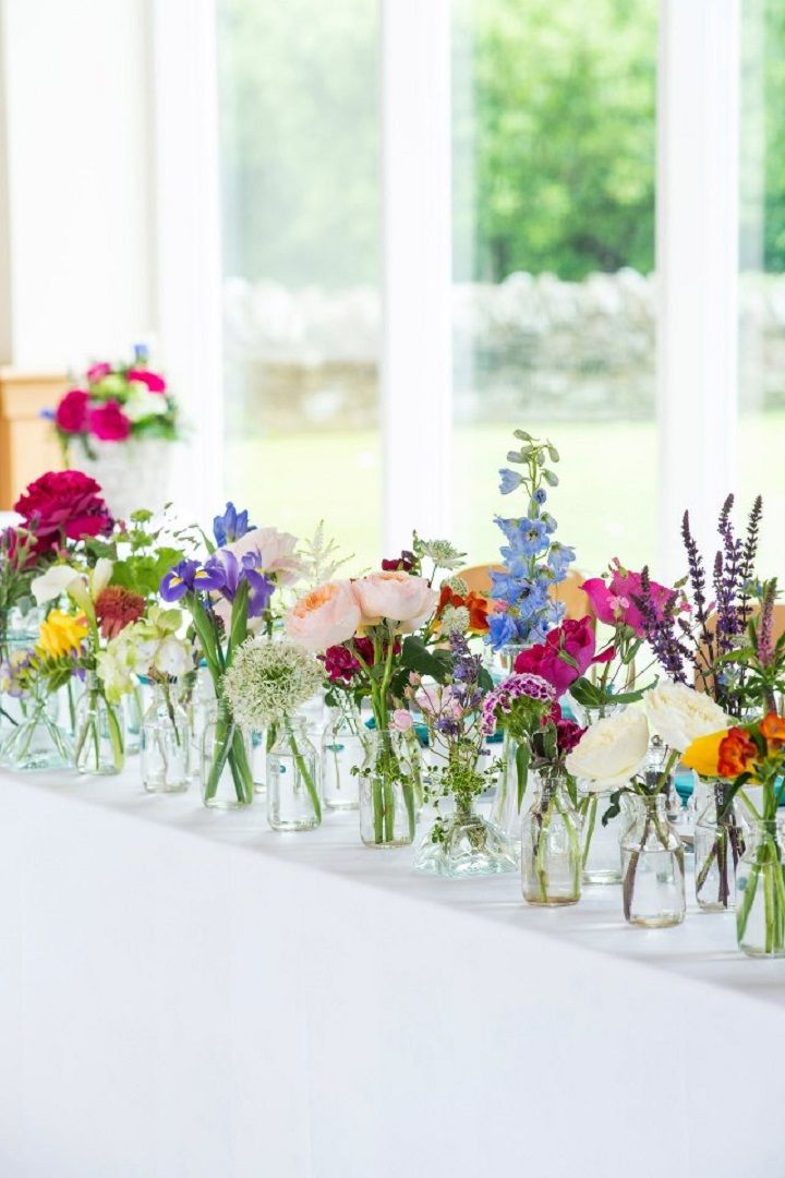 Colourful flowers filled in bottles different sizes and styles #centrepieces #bottlecenterpieces #rusticcenterpieces