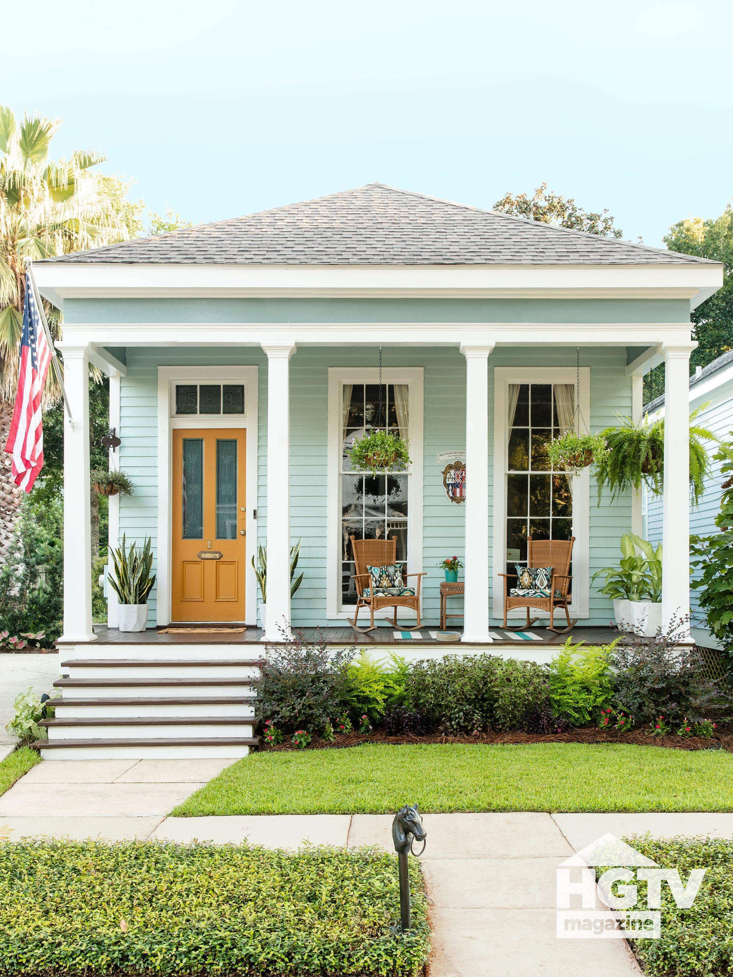 This adorable house in Alabama is decorated with an orange door, wicker chairs and blue accessories. See more on HGTV.com.