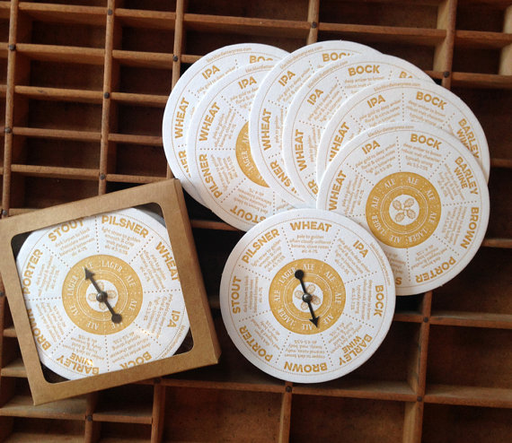 """Spinner Beer Coasters. Set of 6 round coasters, letterpress printed, with 8 beer styles and descriptions. Each set is boxed in a kraft box and includes a spinner coaster with a little metal spinning arrow, perfect for when you can't make up your mind what beer to try! Coasters are 4"""" in diameter."""