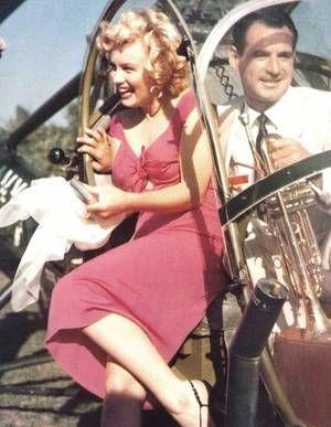 """On termine cette année 1952, qui fut riche en évènements et pour la notoriété montante de Marilyn grâce à son dernier film """"Niagara"""", avec la fête du musicien Ray ANTHONY (The Ray ANTHONY party) / La fête s'est tenue dans une villa de Sherman Oaks, dans le district de Los Angeles, situé dans la vallée de San Fernando. Marilyn, vêtue de la robe rouge du film """"Niagara"""", est arrivée en hélicoptère, puis s'est prêtée au jeu des photographes en faisant mine de jouer de la trompette et de la…"""