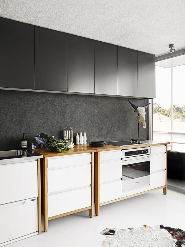 Natural materials and textures soften the sleek black cabinetry, giving the…