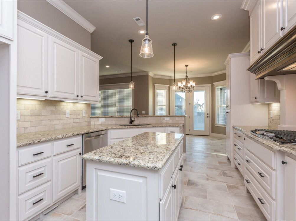 Spacious white kitchen with light travertine backsplash and ...
