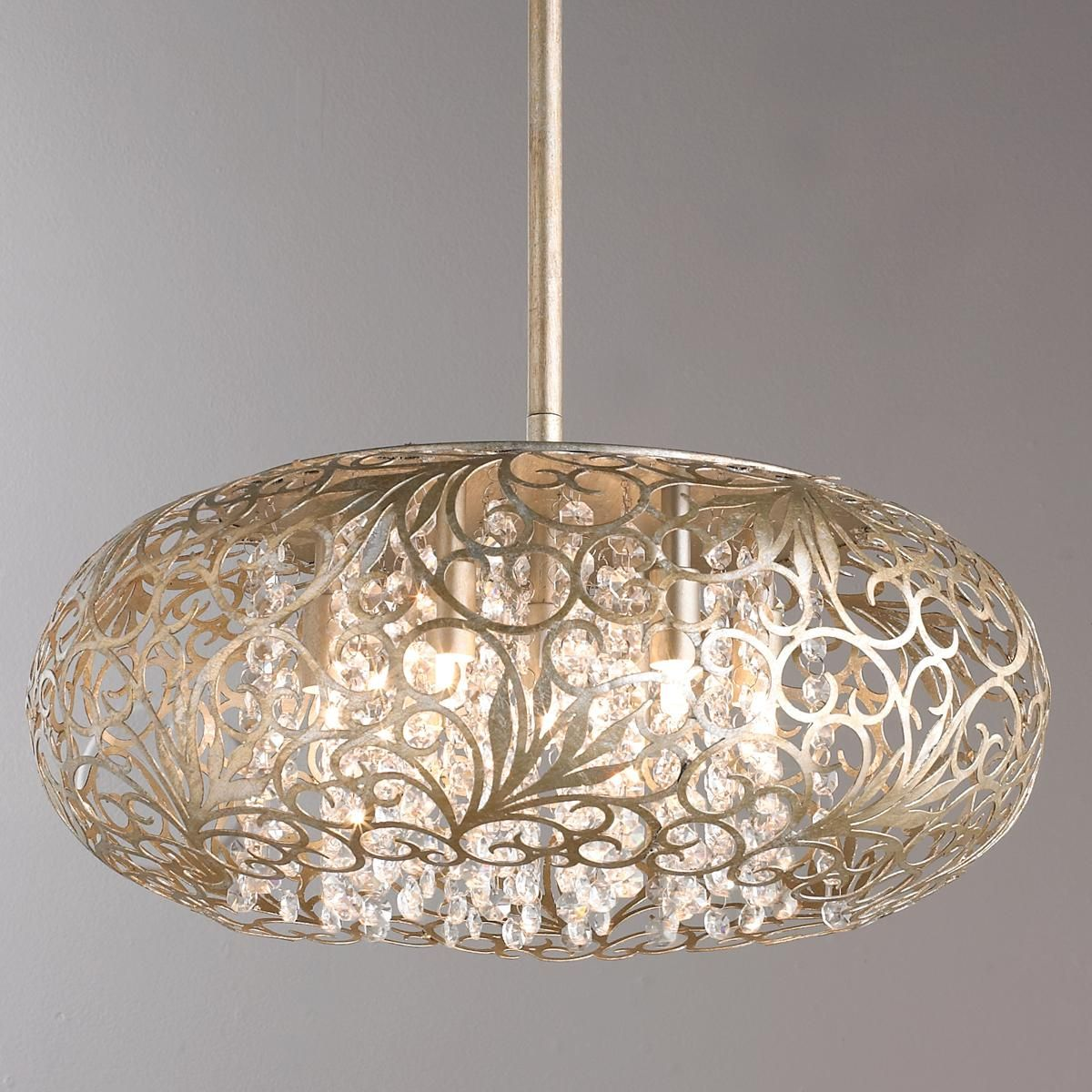 "Arabesque Crystal Pendant Chandelier The intricate patterns of this pendant light are formed in metal and finished in Golden Silver. Strands of crystal beads add sparkle as they shimmer through the Xenon lamps. The unique cut out shape adds a touch of class to any room. 7x50 watt G9 Xenon frosted bulbs included. (8""Hx18""W)"