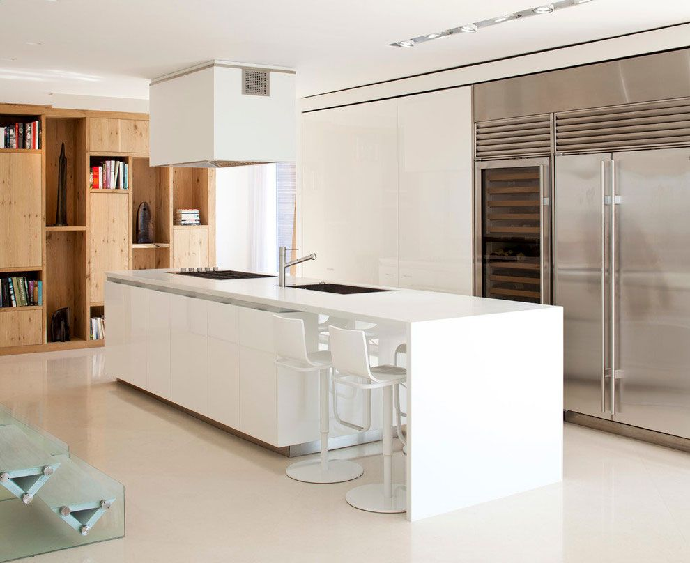 White kitchen island with bar area and induction cooktop   With ...