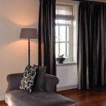 donkere gordijnen geven hier een mooi contrast en door de warme kleur vloer juist sfeervol stoffen chaise longue
