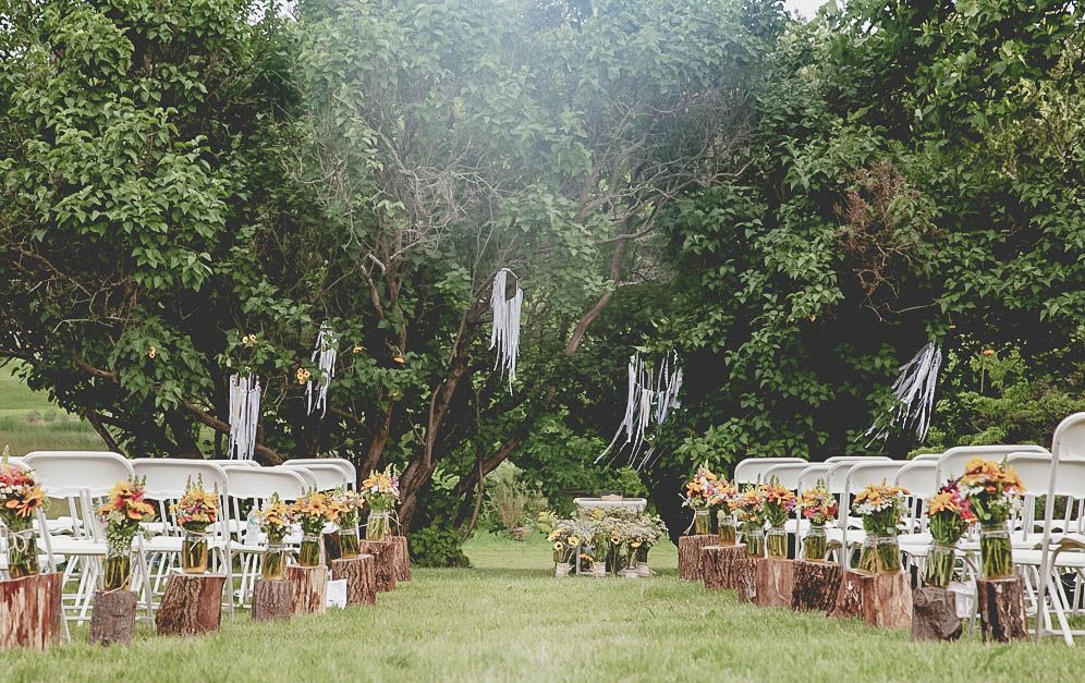 #ringsontheizings Whimsical Wedding- Ceremony Aisle & Gathering: woodland, whimsical, fairy tale, summer, outdoors, happily ever after, wildflowers, rustic, horse ranch decor, barn, tree trunk stumps, light energy   Photographer: Taja Sparks Ari-Drive