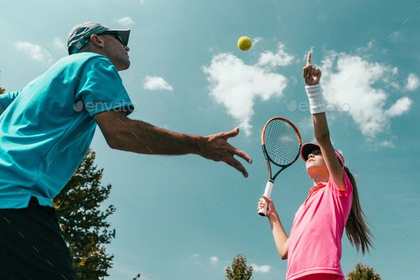 Tennis training by microgen Tennis instructor with young girl on tennis training