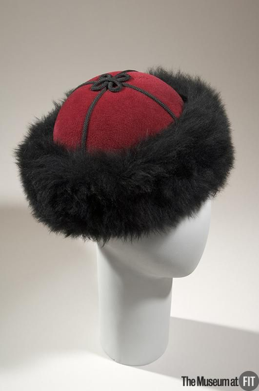 Hat | Yves Saint Laurent (French, 1936-2008 | France, 1976 | Materials: burgundy velour felt, black faux fur and cording | Saint Laurent introduced his seminal 'Ballet Russes' collection in 1976, melding Russian-inspired folklore and fantasy to create lavish yet wearable clothes and accessories, such as this fur-trimmed hat. This collection was one of Saint Laurent's most acclaimed, and it re-established the significance of the haute couture | The Museum at FIT, New York