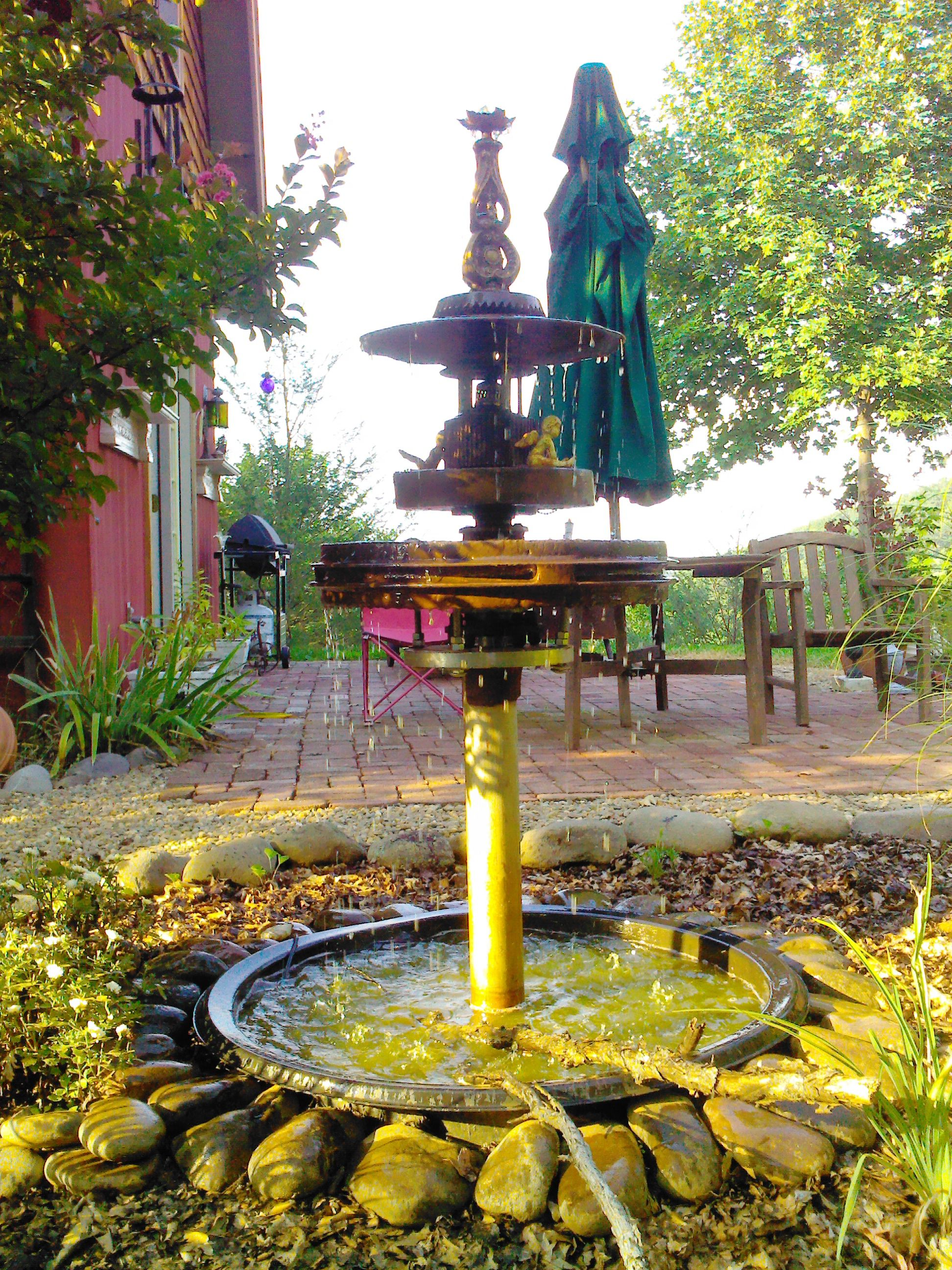 fountain i made from scrap metal  basin is a front tractor tire hub  next level up is a