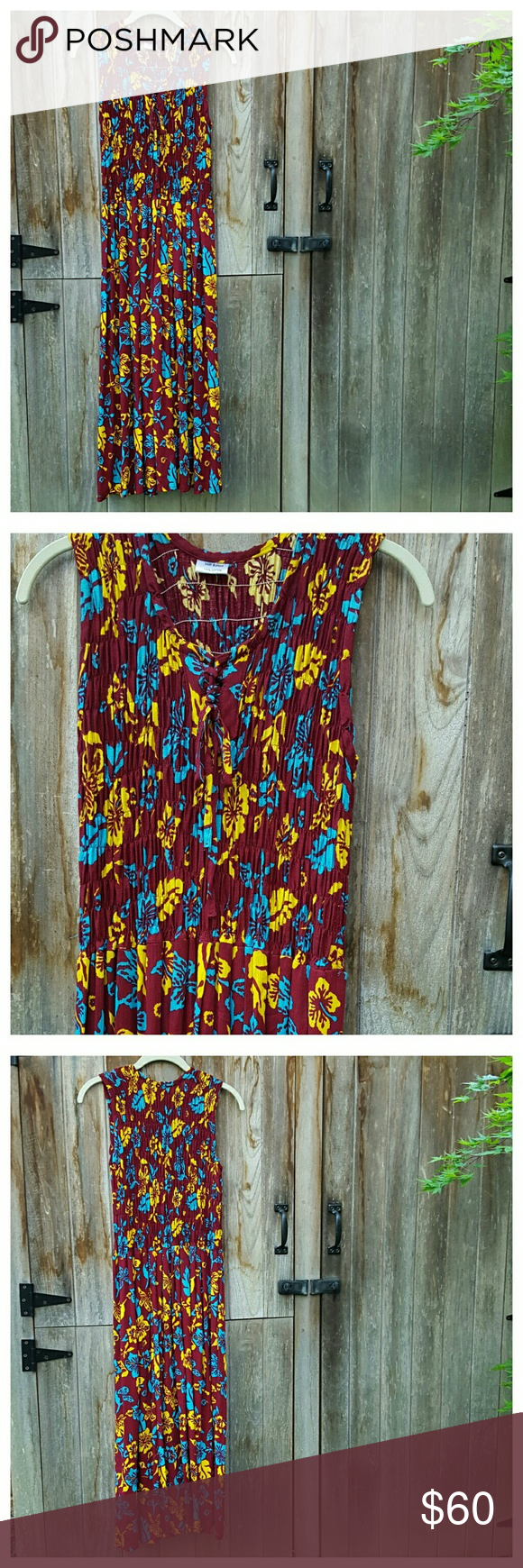 """Tropical Print Smocked Maxi Dress Bright, breezy dark red maxi dress with blue and yellow tropical floral print. Sleeveless with round neck. smocked bodice and lace-up front. Pullover styling. No size tag but sold as size S. Length from back of neck 47"""" width at bust and waist 13"""" unstretched, stretches to 21.5"""". 100 % cotton. EUC. Dresses Maxi"""