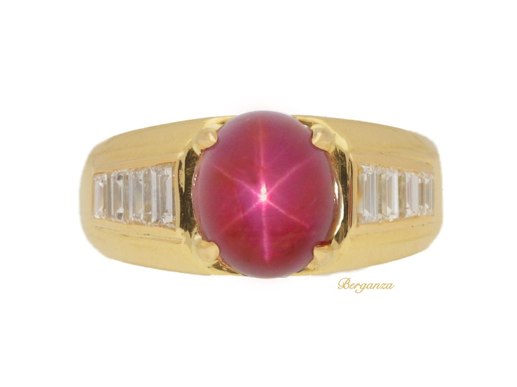 Van Cleef & Arpels Burmese star ruby and diamond ring. Set centrally with a oval cabochon natural unenhanced Burmese star ruby in an open back four claw setting with an approximate weight of 4.97 carats, flanked by eight rectangular baguette cut diamonds in open back rubover channel settings with a combined approximate weight of 0.80 carats, to broad integrated shoulders, geometric pierced backholing and a tapering solid D-shape shank.